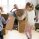 Two kids holding moving boxes keep running to their parents.