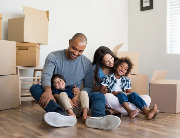 A happy family sitting on the floor with a lot of moving boxes on background waiting for movers dc