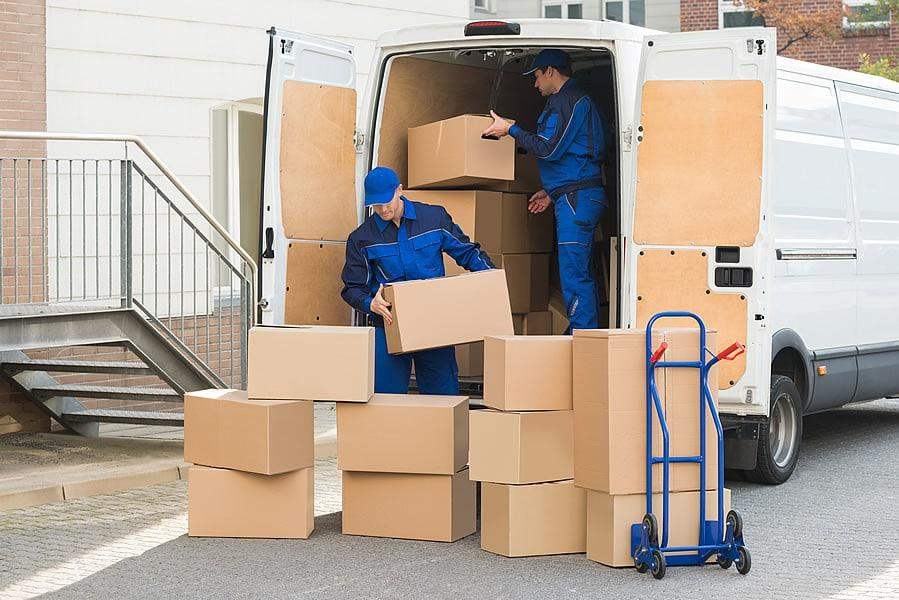 two men are putting lots of boxes in a moving van