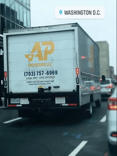 A white van on which is written AP Pro Moving drives along the streets of Washington, DC