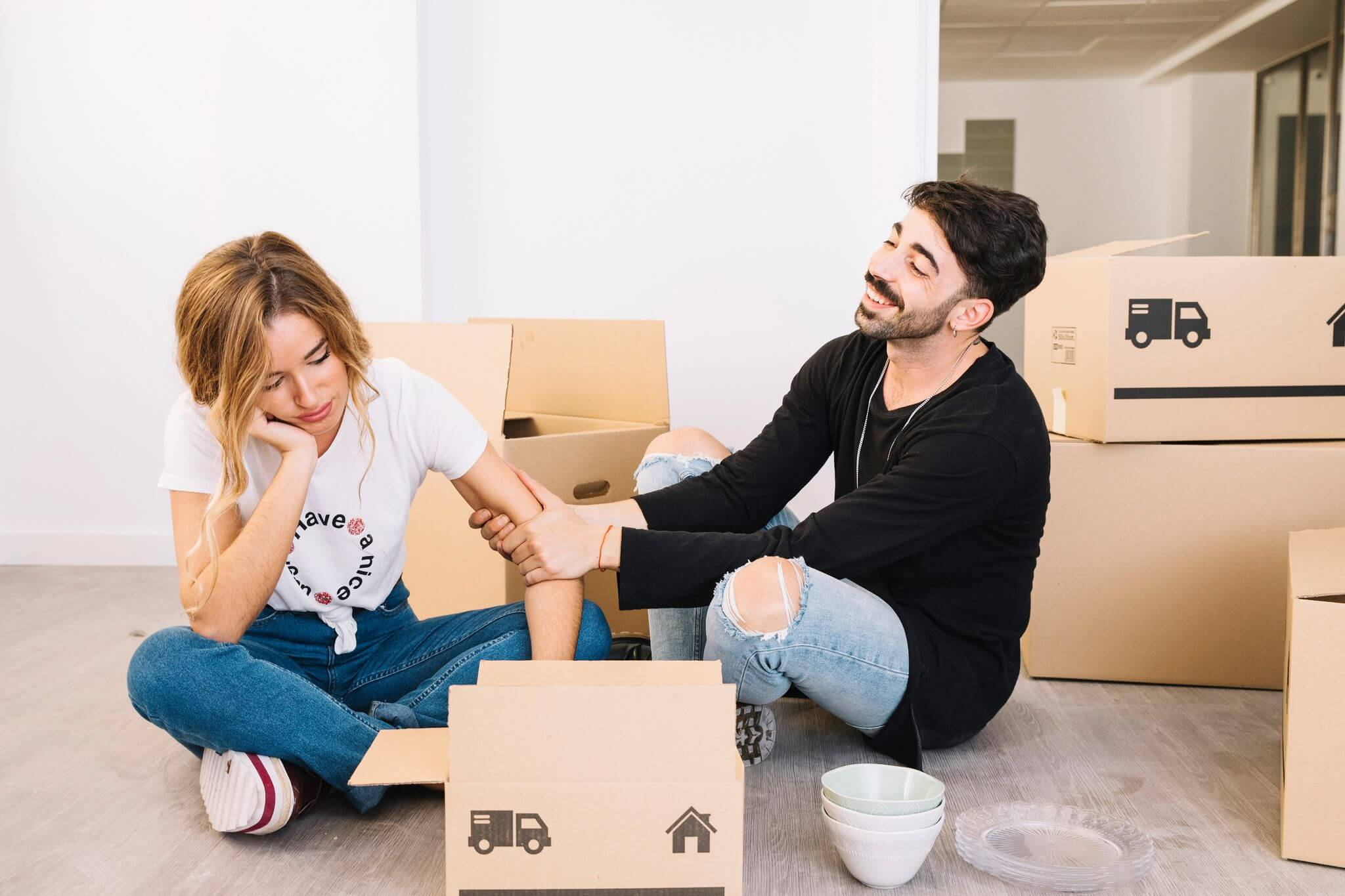 Man ad woman sitting on the floor with a lot of boxes on background waiting for movers arlington va